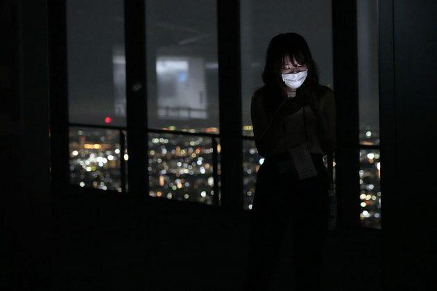 Obyvatelka Tokia sleduje zahájení LOH 2021 z vyhlídkové věže ve čtvrti Šibuja.