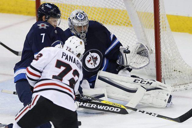 Brankář Winnipegu Ondřej Pavelec (31) chytá pokus Arťemi Panarina (72) z Chicaga v zápase NHL.