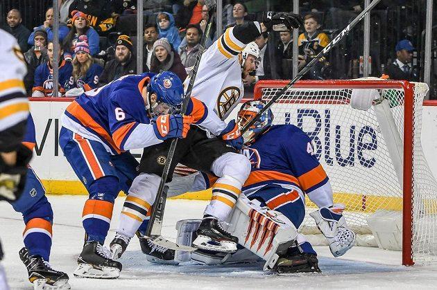 David Krejčí (46) z Bostonu padá na slovenského brankáře Jaroslava Haláka (41) z New Yorku Islanders.