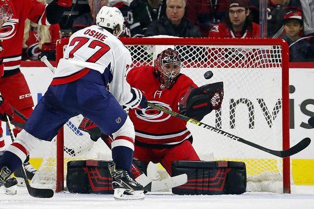 Petr Mrázek v brance Caroliny chytá puk před dojíždějícím T.J. Oshiem (77) během zápasu NHL s Washingtonem.
