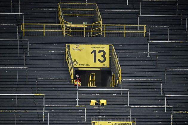 Steward na jinak opuštěné tribuně sleduje přípravy na derby Dortmund - Schalke.