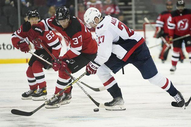 Hokejista Washingtonu Capitals Alexander Alexeyev (27) bojuje o puk s útočníkem New Jersey Pavlem Zachou.