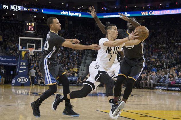 Jeremy Lin z Brooklynu v souboji s Válečníky Stephenem Currym a Draymondem Greenem během třetí čtvrtiny v Oracle Aréně.