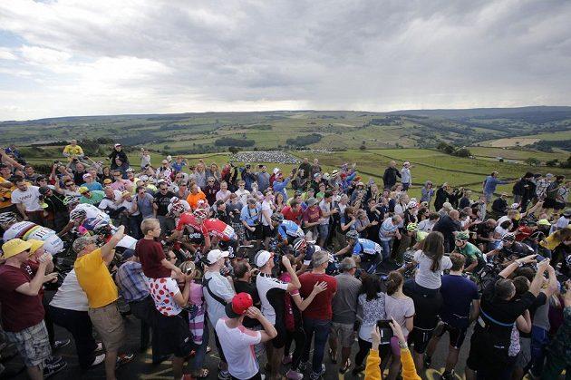 Cyklisté projíždějí špalírem diváků při druhé etapě Tour de France.