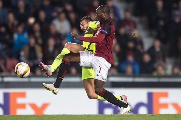 Sparťanský fotbalista Kehinde Fatai v souboji s obráncem Tripolisu Kostasem Giannoulisem během utkání Evropské ligy.