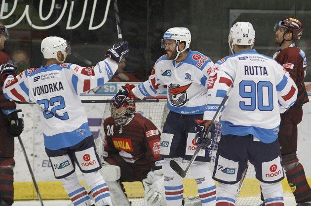 Chomutovští hráči (zleva) Michal Vondrka, Michal Poletín a Jan Rutta se radují po vstřeleném gólu, uprostřed brankář Sparty Tomáš Pöpperle.