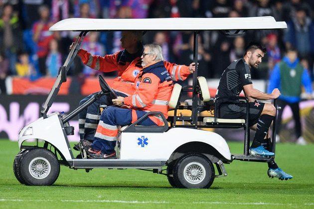 Zraněný David Hovorka ze Slavie Praha odjíždí z hřiště během utkání v Plzni.