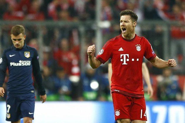 Xabi Alonso poslal Bayern do vedení. Vlevo je zklamaný útočník Colchoneros Antoine Griezmann.