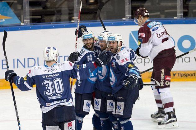 Hokejisté Plzně (zleva) Jakub Lev, Erik Hrňa, Ondřej Kratěna a Nicholas Johnson se radují z gólu proti Spartě. Vpravo zklamaný Michal Čajkovský ze Sparty.