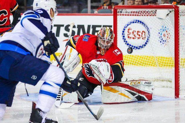 Gólman Calgary Flames David Rittich (33) v akci během utkání NHL s Winnipegem Jets. Zakončovat zkouší centr Andrew Copp (9).