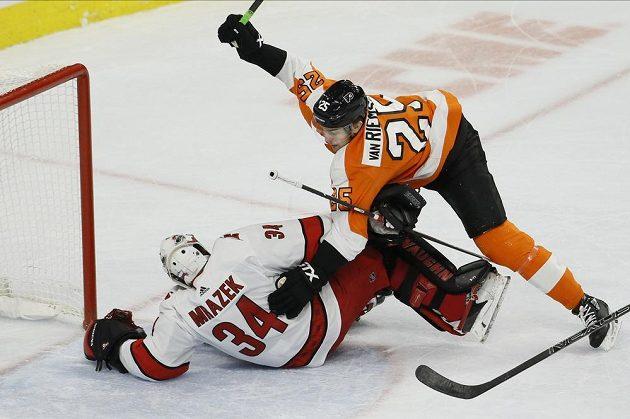 Útočník Philadelphie Flyers James van Riemsdyk (25) narazil do brankáře Caroliny Hurricanes Petra Mrázka.