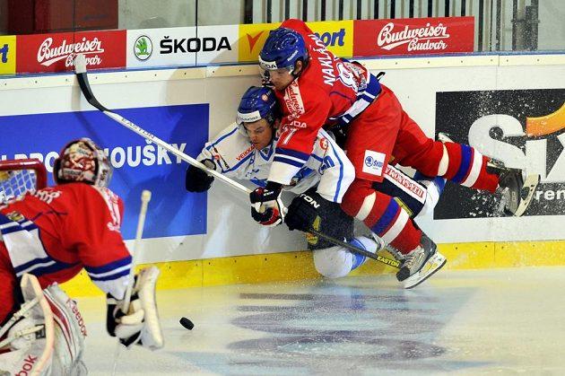 Brankář české hokejové reprezentace Jakub Kovář (vlevo) sleduje souboj mezi finským útočníkem Aaltonenem a obráncem Nakládalem (vpravo).