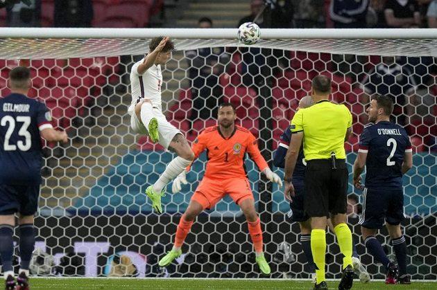 Angličan John Stones ve výskoku posílá hlavou míč do tyče skotské brány.