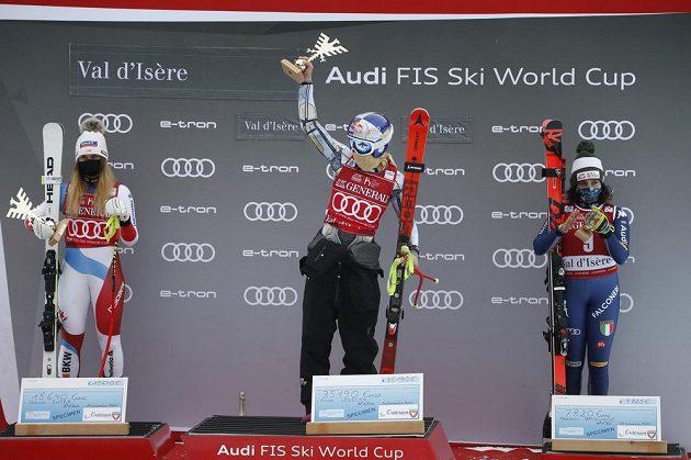 Ester Ledecká (uprostřed) na pódiu pro nejlepší závodnice super-G. Vlevo druhá Corinne Suterová ze Švýcarska, vpravo třetí Federica Brignoneová.