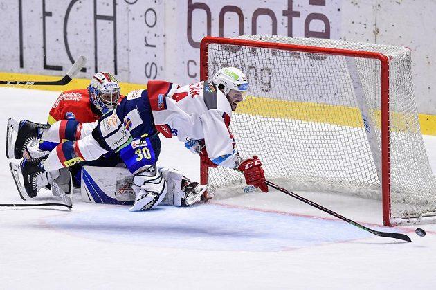 Brankář Českých Budějovic Petr Kváča sleduje, jak pardubický hokejista Brian Ihnačák naloží se svým zakončením v utkání baráže o extraligu.