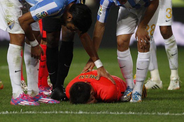 Barcelonský útočník Lionel Messi leží po zákroku obránce Málagy Weligtona Oliveiry (není na snímku) na trávníku.
