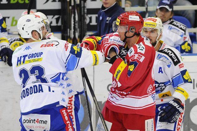 Brněnský útočník Tomáš Svoboda (vlevo) při šarvátce s Danielem Rákosem z Třince. Vpravo přihlíží Jozef Kováčik z Brna.
