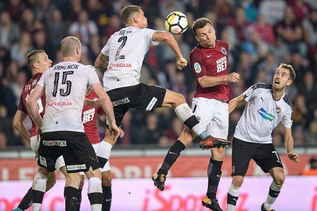 Plzeňský Lukáš Hejda (č.2) a David Lafata ze Sparty Praha ve vzdušném souboji v duelu 10. kola. Plzeňský zadák zasahuje míč rukou.