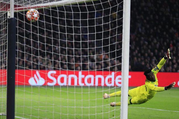 Gólman Ajaxu Andre Onana se marně snaží zasáhnout proti ráně Karima Benzemy v utkání Ligy mistrů.