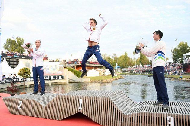 Zlatý skok mistra světa Ondřeje Tunky. Tleskají i stříbrný reprezentační kolega Vít Přindřiš (vlevo) a bronzový Slovinec Peter Kauzer.