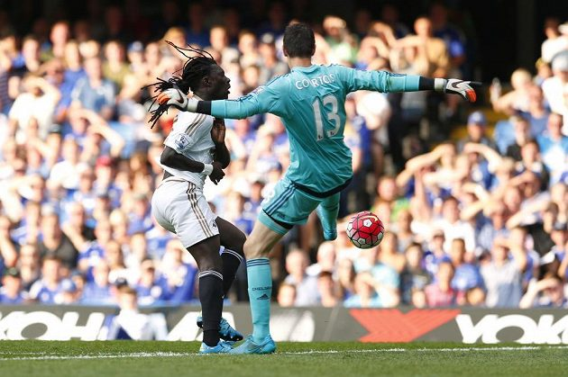 Brankář Chelsea Thibault Courtois v souboji s Bafétimbi Gomisem ze Swansea.