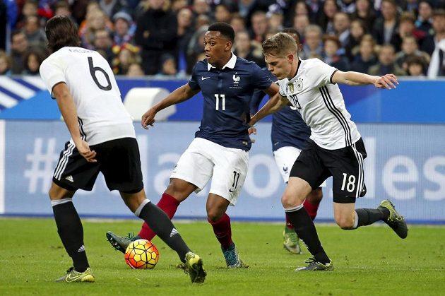 Francouzský útočník Anthony Martial (uprostřed) v obležení dvou německých soupeřů během přátelského utkání.