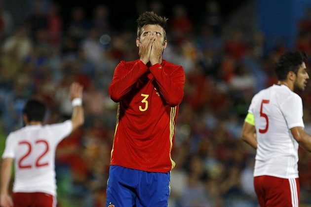Zatímco obránce Španělska Gerard Piqué si schovává tvář v dlaních, za ním slaví hráči Gruzie historické vítězství.