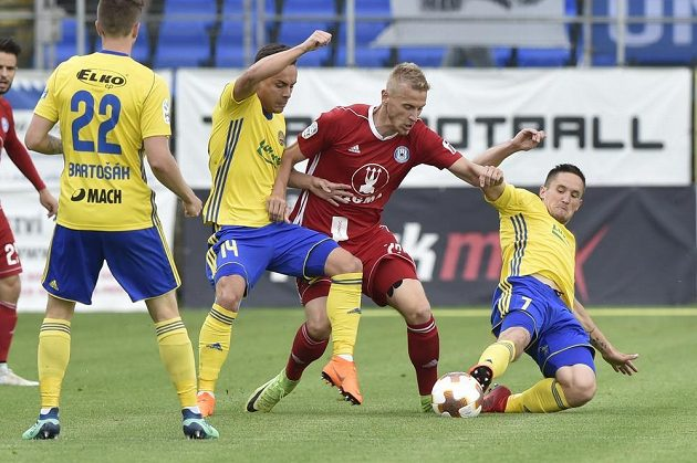 Zlínští fotbalisté Lukáš Bartošák a Daniel Holzer se snaží zastavit olomouckého Uroše Radakoviče. Situaci v utkání 28. kola HET ligy přihlíží Lukáš Železník ze Zlína.