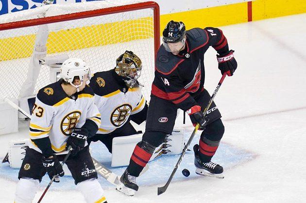 Křídelník Caroliny Hurricanes Justin Williams (14) zkouší tečovat puk před brankou Bostonu Bruins, kterou střežil slovenský gólman Jaroslav Halák (41).
