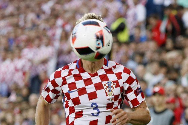 Míč před chorvatským fotbalistou Ivanem Striničem v osmifinále ME proti Portugalsku.