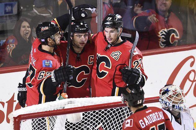 Hokejisté Calgary Mark Giordano (5), Michael Frolík (67) a Sean Monahan (23) se radují z gólu proti Washingtonu, jemuž ale podlehli vysoko 2:6.