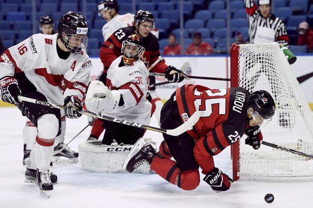 Kanaďan Jordan Kyrou padá po nedovoleném zákroku Nica Grosse ze Švýcarska (vlevo) ve čtvrtfinále MS hokejistů do 20 let v Buffalu.