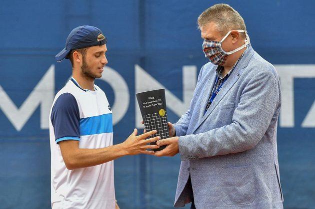 Michael Vrbenský přebírá od prezidenta Českého tenisového svazu (ČTS) Ivo Kaderky trofej pro vítěze.