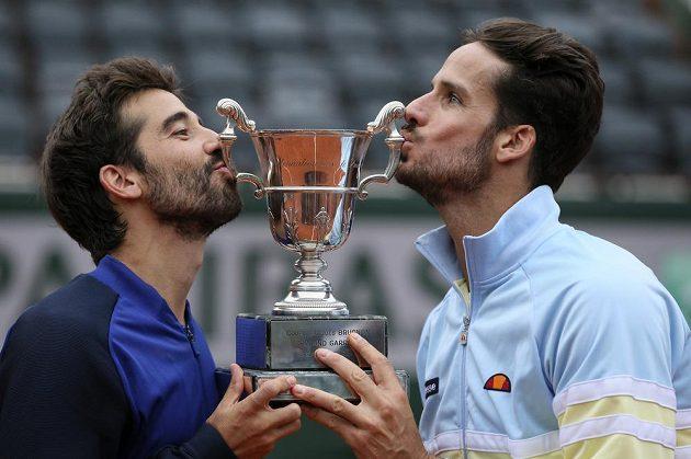 Španělé Feliciano López (vpravo) a Marc López s trofejí pro vítěze French Open.