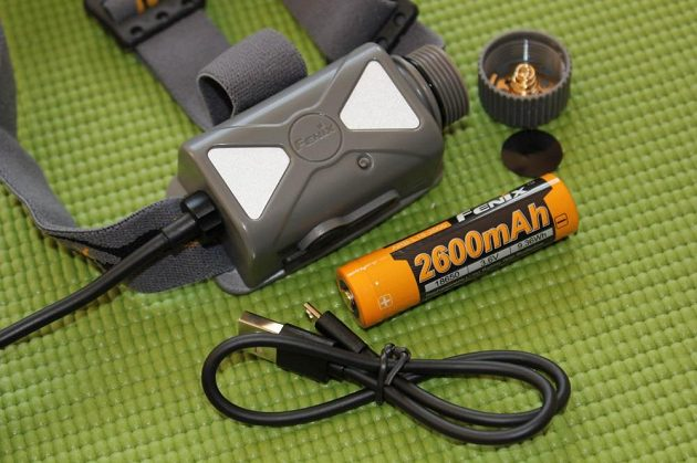 Čelovka Fenix HP25R: Otevřené bateriové pouzdro, dodávaný akumulátor a nabíjecí kablík.
