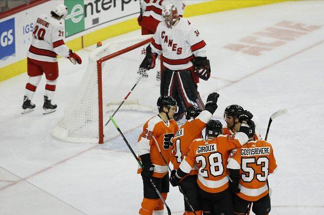Hokejista Philadelphia Flyers Sean Couturier (14) slaví se spoluhráči gól, který vstřelil Petru Mrázkovi z Caroliny Hurricanes.