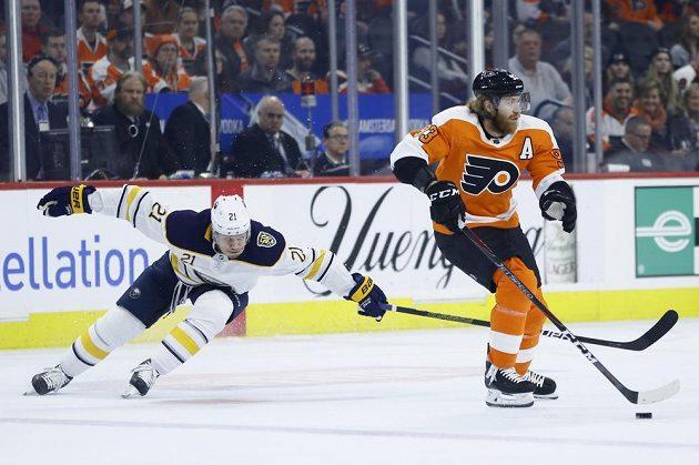 Kyle Okposo (vlevo) z Buffala se snaží sebrat kotouč českému útočníkovi Jakubovi Voráčkovi v zápase NHL.