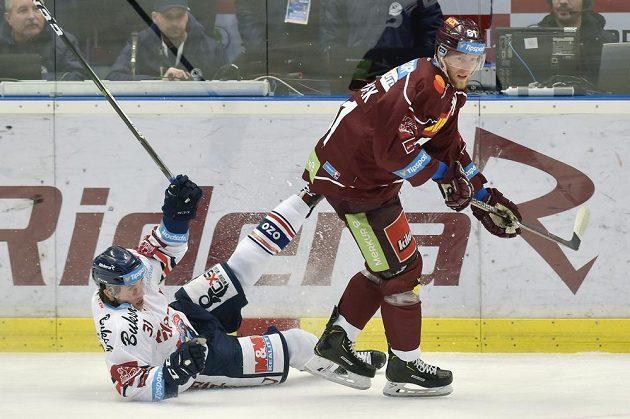 Vítkovický hokejista Tomáš Guman leží na ledě po souboji se sparťanem Lukášem Klimkem v utkání předkola play off.