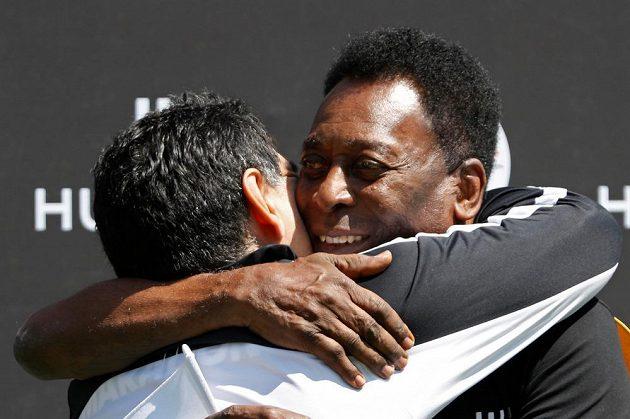 Někdejší výteční fotbalisté Pelé a Diego Maradona (zády) v objetí.