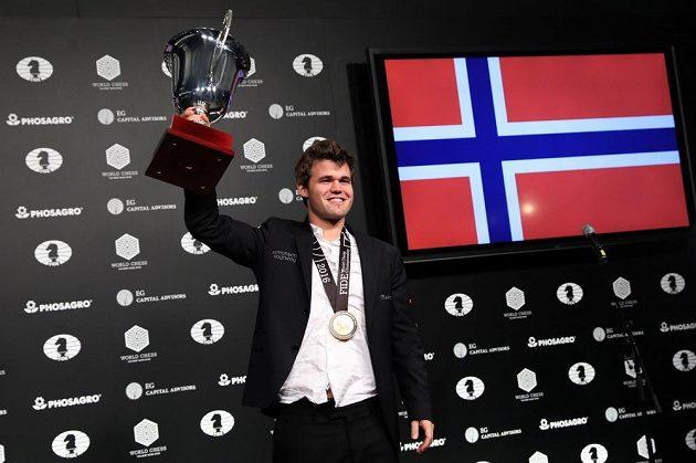 Nor Magnus Carlsen s trofejí pro šachového šampióna.