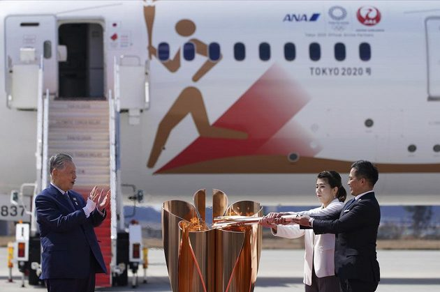 Olympijský oheň je v Japonsku. Trojnásobný olympijský vítěz Tadahiro Nomura (vlevo) a držitelka tří zlatých medailí Saori Jošidaová s olympijským ohněm po příletu do pořadatelské země olympiády. Šéf organizačního výboru Jošihiro Mori (vlevo).