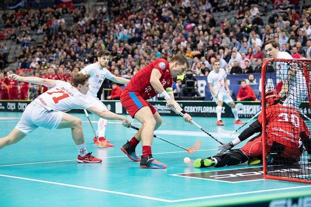 Matěj Jendřišák (uprostřed) a Tobias Heller ze Švýcarska během utkání v základní skupině Mistrovství světa ve florbale