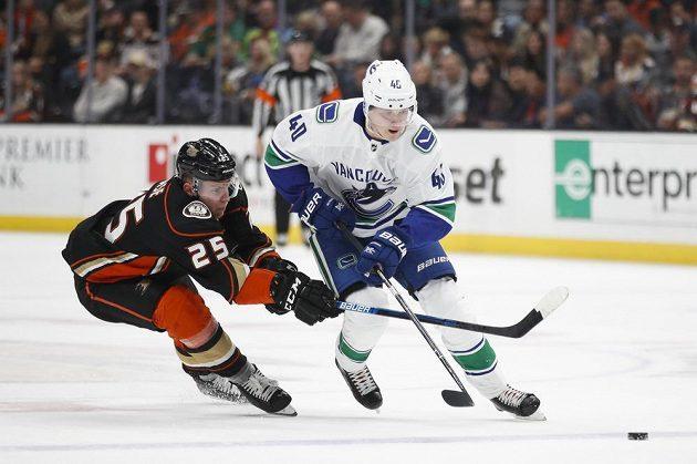 Český útočník Ondřej Kaše z Anaheimu se snaží zastavit Eliase Petterssona z Vancouveru v utkání NHL.