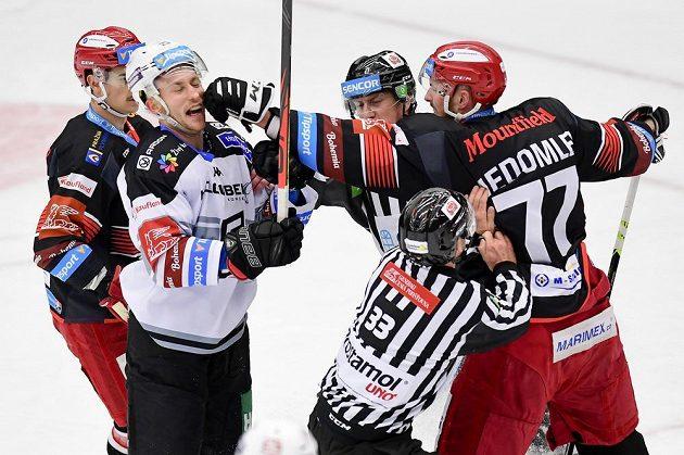 Zleva Jordann Perret z Hradce Králové, Tomáš Mikúš z Karlových Varů a Richard Nedomlel z Hradce Králové v akci během utkání hokejové extraligy.
