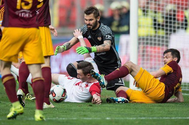 Brankář Dukly Praha Filip Rada se vrhá po míči, vedle něj je na zemi obránce Dukly Jan Šimůnek, gólmanovi brání Jaromír Zmrhal ze Slavie. Derby v Edenu skončilo 2:2.