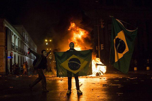 Demonstranti v brazilském Rio de Janeiro před zapálenou barikádou.