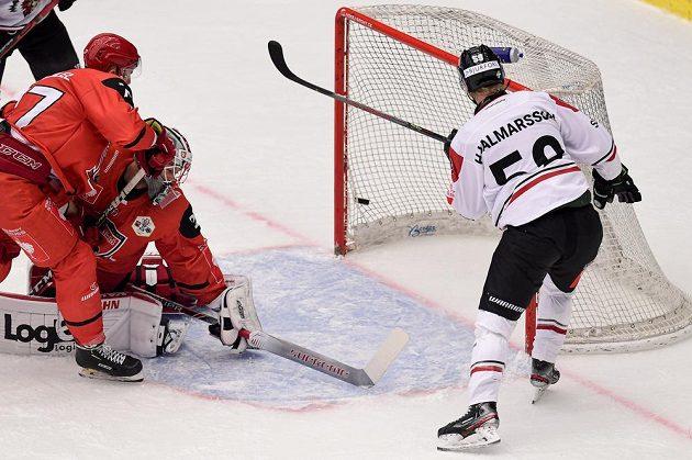 Hokejista Simon Hjalmarsson z Frölundy (vpravo) střílí gól. Zleva přihlížejí Richard Nedomlel a brankář Marek Mazanec, oba z Hradce Králové.