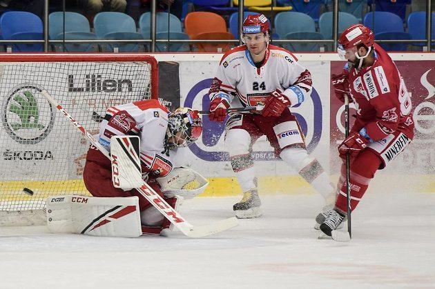 Erik Hrňa (vpravo) z Třince střílí gól na ledě Hradce Králové, zleva jsou brankář Brandon Maxwell a Petr Zámorský z Hradce Králové.
