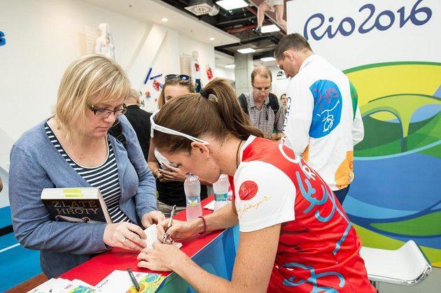 Překážkářka Zuzana Hejnová se podepisuje fanynce.