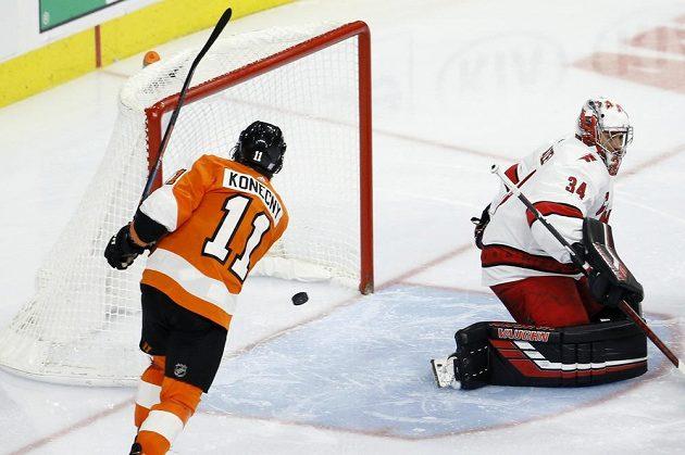 Hokejista Philadelphie Flyers Travis Konecny (11) překonává Petra Mrázka v brance Caroliny.